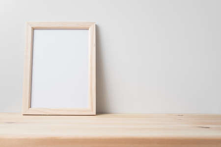 Design concept - front view of vertical wood photo frame on wood floor whit white wall for mockup Standard-Bild