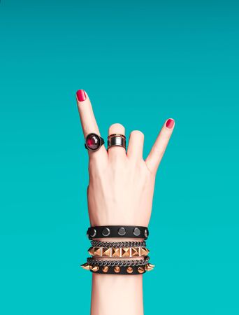 Rock hand sign, female hand punk rock gesture with gold wrist bracelets and finger rings isolated, creative art protest banner, fashion hipster accessories, 3d rendering 版權商用圖片