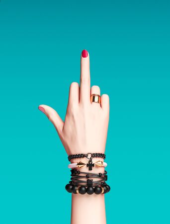 Fuck you hand sign. Bad girl gesture with gold wrist bracelets and finger rings isolated, creative art protest banner, fashion hipster accessories, 3d rendering
