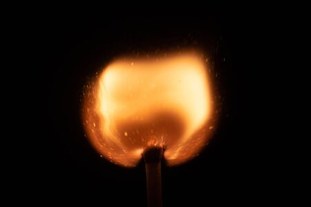 Ignition of match with sparks isolated on black background