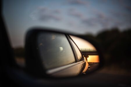 susnet reflection seen through car side mirror highway space for text travel family fun concept
