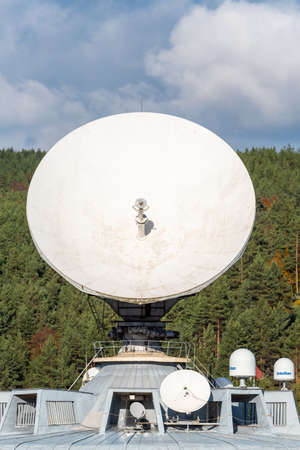 Detail of a giant radio telescope dish pointed skyward on clear blue sky background technology