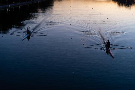 赛跑在运河水库的皮船划艇运动实践在日落充满活力的背景