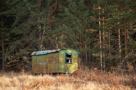 Long ago abandoned trailer forgotten in the woods high contrast autumn landscape with copy space for text advert