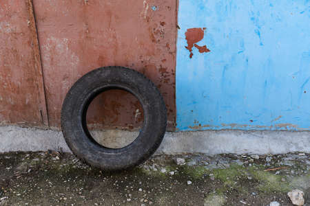 An old worn out tyre leaning against a wall in a poor neighbourhood suburb Archivio Fotografico