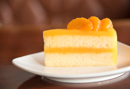 Orange cake on plate with blur brown background