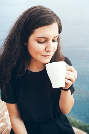 strengthen: Beautiful young woman is drinking delishes tea on a balcony with sea view. Daily cup of tea. Early morning routine. Pleasure, hydrating the body. Strengthen your immune system