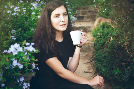 owning: Young smiley woman is drinking floral tea in her garden and dreaming about plans for the future. Feeling harmony with life and nature