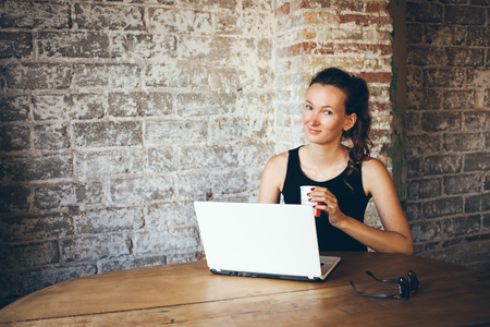 communicates: Casual smiley young woman with dark hair is using laptop for distance job at coffee shop. Portrait of an attractive girl who communicates online on her PC