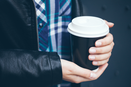 Young woman is drinking coffee on the street while walking in the city centre. Close-up of hands with take away cup of hot coffee. Copy-space blank for your advertisement text or design content Zdjęcie Seryjne