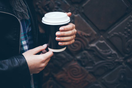 Young woman is drinking coffee on the street while walking in the city center. Close-up of hands holding take away cup of hot coffee. Copy-space blank for your text or advertisement