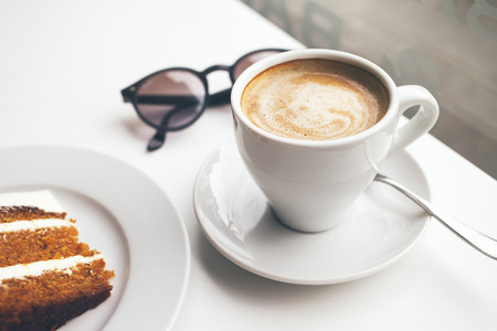 Close-up of cup of coffee on the white table. Morning, drinking coffee and eating dessert. Relaxing mood, break time. Zdjęcie Seryjne