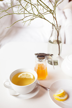 Cup of hot green tea with lemon on white table, fresh lemon and honey - closeup shot. Sun light flair effect. Nice interior in wooden house. Relaxation concept. Stock Photo