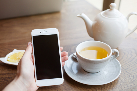 Cropped view of female hand holding smart phone with blank screen for your text. Woman reading messages on cell phone with cafe interior background while drinking hot cup of tea with lemon
