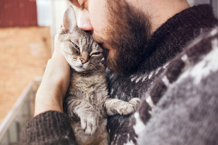 Close-up of happy young man who is standing on a balcony with his cat. Home pets. Beard man in icelandic sweater is holding and kissing his cute curious Devon Rex cat. Standard-Bild