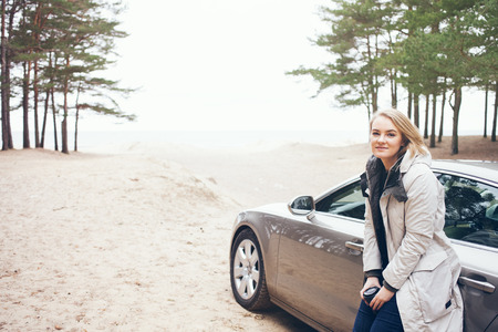 Happy woman next to car, relaxing on road trip adventure travel. Resting after having long distance car trip wile parking near on the seashore away from the city and drinking hot cup of take-away coffee