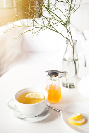 Cup of hot green tea with lemon on white table, fresh lemon and honey - closeup shot. Sun is shining through the window, warm feeling. Relaxation and enjoying live concept