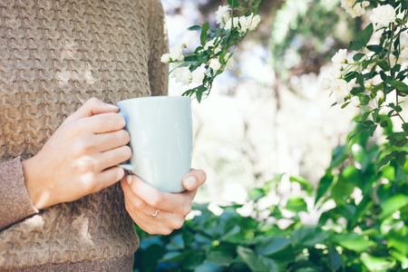 Young Caucasian woman drinks morning coffee from big blue cup being outdoor in spring blossoming garden. Close-up outdoor photo, selective focus on hand. Blank copy-space for your text or advertisement content Zdjęcie Seryjne