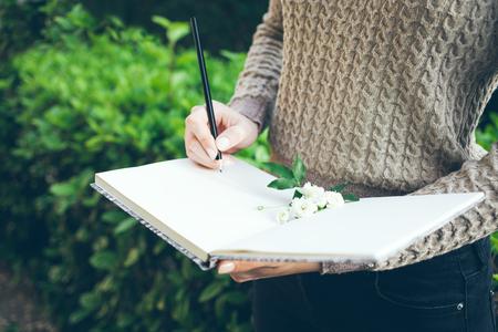 Cercando un'ispirazione mentre si cammina all'aperto nel parco verde di primavera / giardino. Close-up di mani di giovane donna che descrive le sue speranze e sogni di futuro nel suo diario, rendendo piani. Pianificatore da fare.