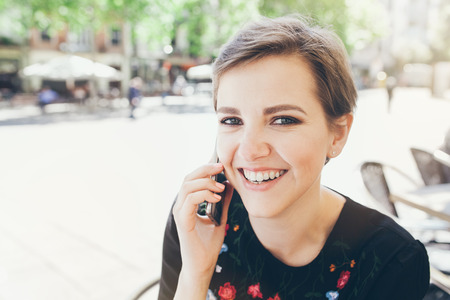 Close-up portrait of attractive young Caucasian woman talking on mobile phone at outdoor cafe. Girl talking by mobile phone, smiling. Sunny day. Outdoor photo. Zdjęcie Seryjne
