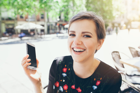 Girl with short pixie haircut is having a phone conversation. People and technology concept. Happy and cheerful expression. Zdjęcie Seryjne