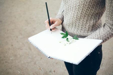 Woman hand with pencil writing on notebook. Writer looking up for inspiration to compose new poem.