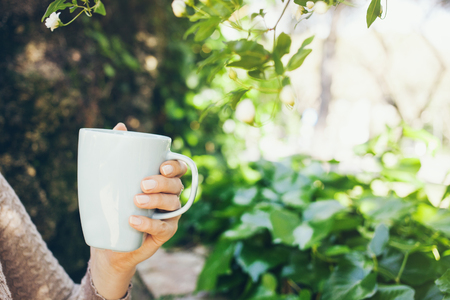 Close-up of woman hand with cup of coffee. Early morning routine. Green garden on the background. Selective focus, film effect .