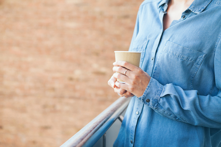 Young woman in blue casual jeans shirt is drinking coffee. Close-up of hands holding paper take away cup of hot coffee. Copy-space blank for advertisement content. Brick wall on the background Zdjęcie Seryjne
