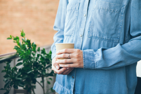 Young woman in blue casual jeans shirt is drinking coffee. Close-up of two hands holding take away cup of hot coffee. Copy-space blank for advertisement content. Brick wall on the background