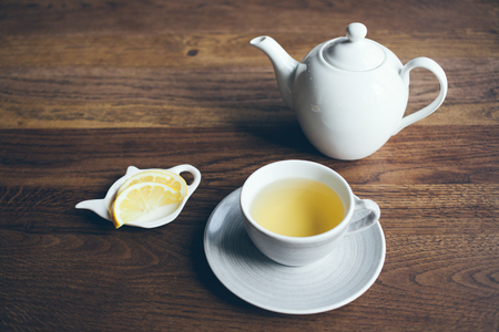 Close-up shoot of cup of hot tea with lemon and infusion teapot on brown wooden table. Boost your immune system naturally