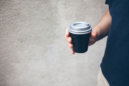 Man is holding black cup of take-away coffee, concrete wall texture on the background. Copy space blank for your text, or advertisement.