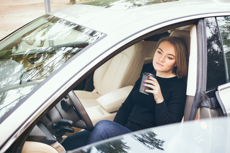 Woman resting in the car from a long journey and drinking takeaway cup of hot coffee, to boost energy.