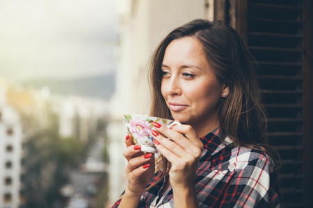Woman is smiling and drinking coffee on a balcony. Close up of a woman holding in hands and cup of coffee. Early morning routine. Selective focus