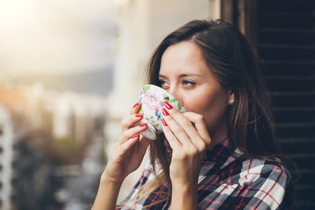Woman is drinking coffee on a balcony. Close up of a woman holding in hands and drinking cup of coffee. Early morning routine Zdjęcie Seryjne