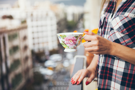 Woman is drinking coffee on a balcony with big city view. Close up of hands with  cup of coffee. Early morning routine Zdjęcie Seryjne
