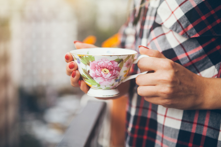 Woman in plaid shirt is drinking coffee on a balcony with city view. Close up of hands with  cup of coffee. Early morning routine, sun light flair effect, selective focus