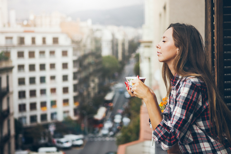 Side view of cheerful young girl looking happy and smiling and drinking cup of appetizing coffee while standing at apartment balcony terrace with an urban view.