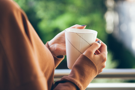 Woman is drinking coffee on a balcony. Close up of hands with white cup of tea. Early morning routine. Selective focus. Blured green background.