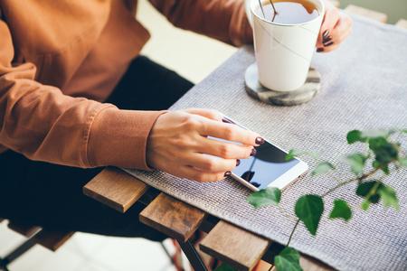 Primer plano de la mano de la mujer sosteniendo una taza de té de cerámica blanca y con smartphone, al aire libre. Leer noticias, navegar por la web / Internet, chatear en la red social en el teléfono inteligente. Fondo borroso.
