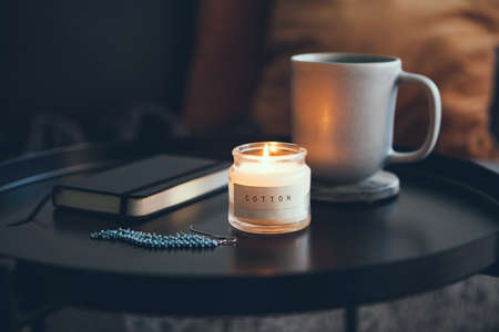 Cozy interior details. Little round table with cup of delicious tea and candle, notepad and beautiful blue color and silver earrings. Business woman resting after busy day. Selective focus. Standard-Bild