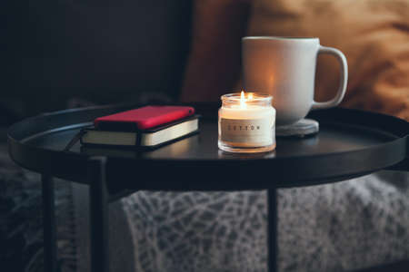 Little black raund table next to the sofa with cup of delicious hot chocalate / cacao drink and candlelight. Relaxing after work mood, offline. Warm natural light, Scandinavian style Standard-Bild