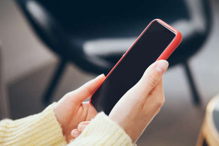 Woman in yellow jumper is holding in hands smart phone, close up image. Standard-Bild