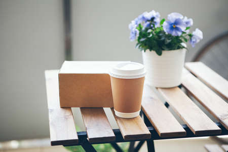 Take away craft paper coffee cup and food box on the top of in out door wooden table, selective focus. Standard-Bild