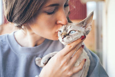 Beautiful woman is kissing her cute blue eyed kitten. Selective focus lifestyle photo