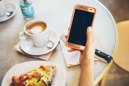 Close-up of woman's hands holding cell phone while drinking coffee and eating vegetable quiche in modern cafe. Reading news, social network, surfing the web / internet in smartphone. Coffee break business. Standard-Bild
