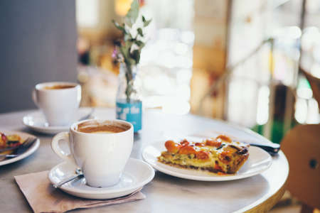 Close-up of a breakfast for two persons in a nice cafe, warm quiche and coffee, no people blurry background. Film effect. Standard-Bild
