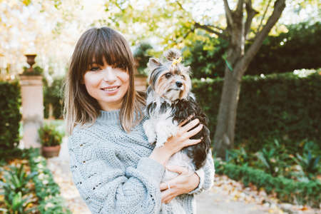 Girl in a casual clothes - gray sweater is walking in the park with her small size dog, nice dry autumn day. Dog is sitting in owners hands feeling happy and looking around. Lifestyle photo. Standard-Bild