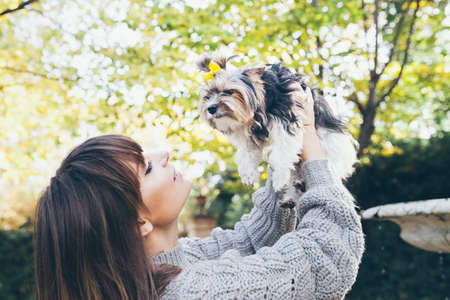 Beautiful woman is walking in the park with cute little puppy. Woman is smiling and holding up in hands little dog. Love and happiness expression. Selective focus.