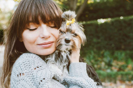 Portrait of a cute girl hugging her little dog. Love and happiness expression. God with the owner feeling good together. Natural light outdoor photo, lifestyle concept Standard-Bild