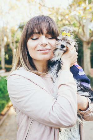 The Biewer Yorkshire terrier rare purebred dog with its owner walking in the beautiful park. Portrait of a cute girl hugging her little dog. Love and happiness expression. Dog in clothes.